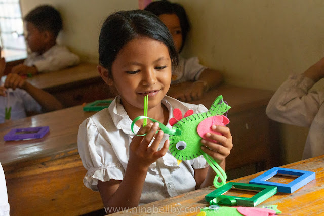 Young Cambodian girl putting together a chicken craft. She is smiling and happy.