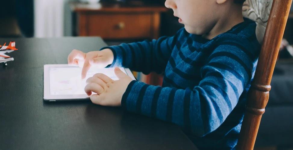 Menino sentado em cadeira mexendo em tablet