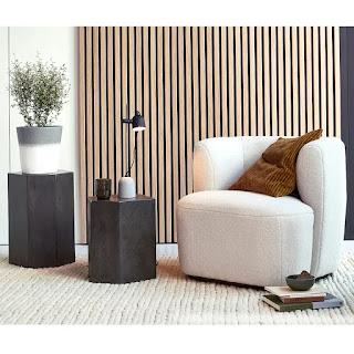 fauteuil blanc en laine bouclée, devant parement en bois, avec tables basses hexagonales en pierre