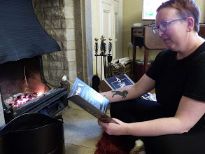 Sarah is sat in front of the fire wearing all black, toasting a marshmallow holding a leaflet