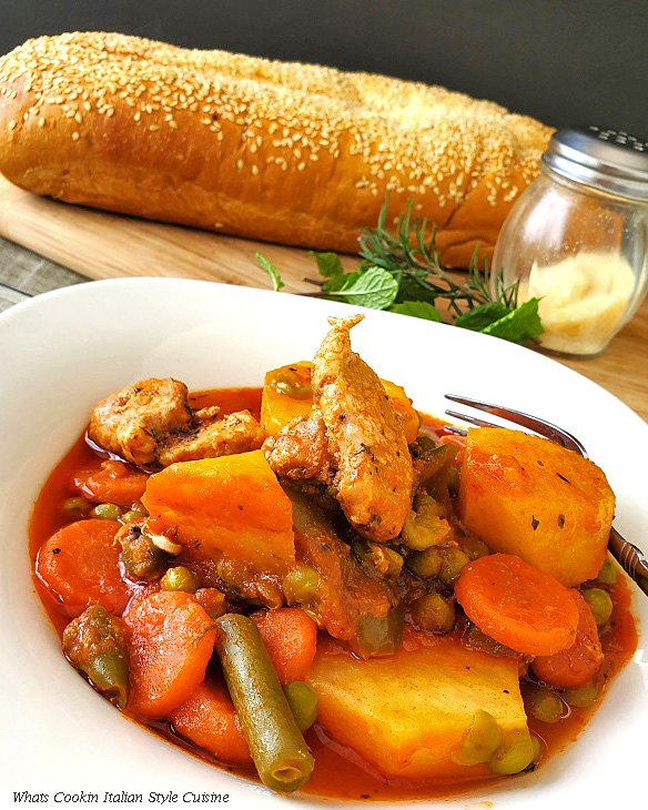 this is a white porcelain bowl filled with Italian stew meat and potatoes in a tomato sauce with bread in the background that has sesame seeds on it