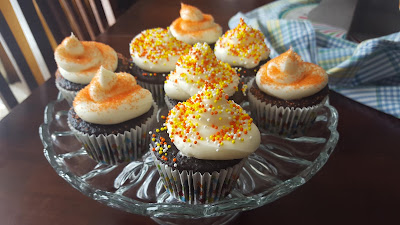 a plate of chocolate cupcakes with white frosting and orange sprinkles