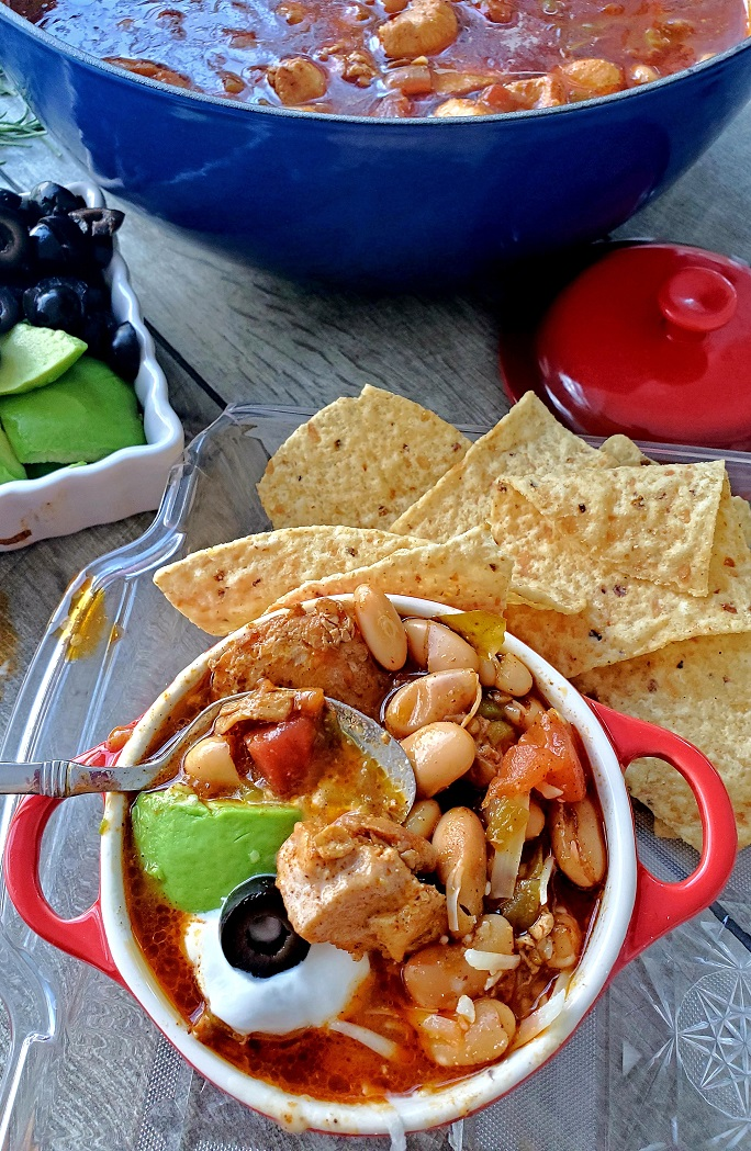 this is a bowl of chicken chili with tortilla chips then topped with olives, cheese, avocado in a red crock