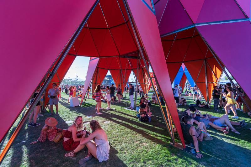 Grupo de gente sentada bajo las torres del Pabellón Sarbalé Ke proyectado para el Festival de Coachella 2019