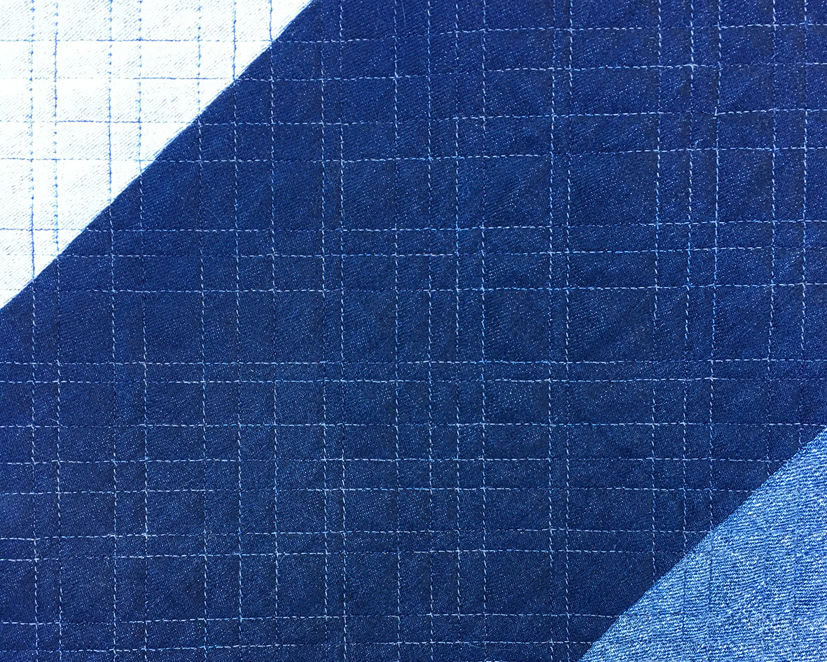 Close up of long arm quilting on a denim quilt