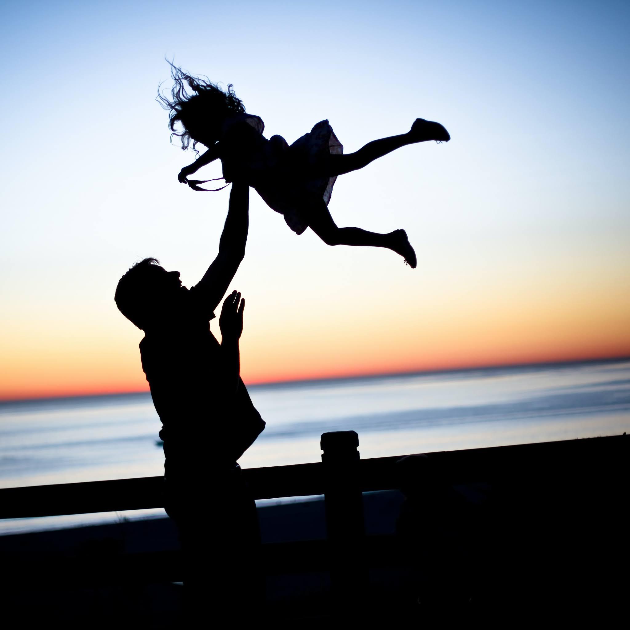 صورة في وقت الغروب لأب يحمل ابنته ويرفعها في الهواء كأنها تطير