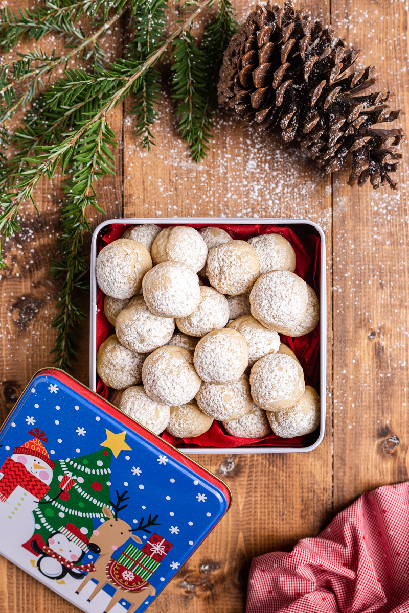 Overhead photo of Keto Snowball Cookies in a Christmas tin on a wooden table.