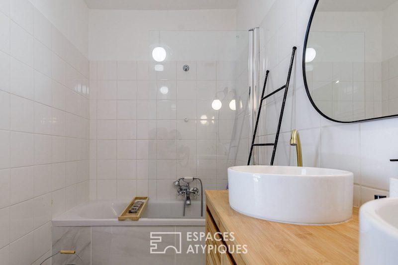 Baño con bañera y encimera de madera.