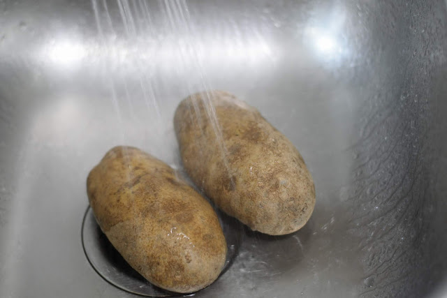 The raw potatoes being washed in a sink.