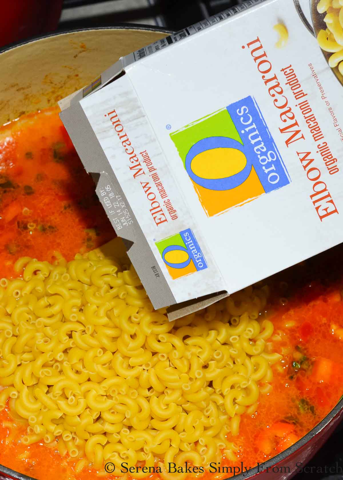 O Organic Macaroni noodles being poured into ground beef mixture with beef broth.