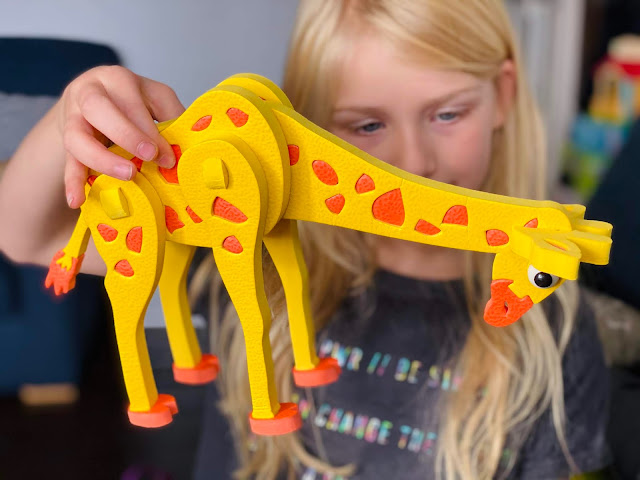 A young girl holding a yellow and orange foam giraffe having assembled the puzzle from lots of different flat pieces. The giraffes neck is pointing down