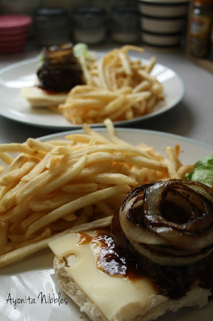 Close up shot of slow cooker BBQ burger with cartelized onions on top with a side of French fries.