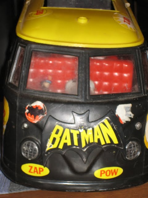 Close-up of Mobile Bat Lab, a.k.a. the Batvan, from the front showing old, scratched-up decals of Batman logo, insignia, and sound effects