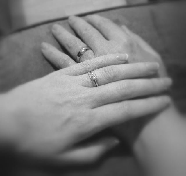 two hands on top of each other. the female hand has a wedding ring and engagement ring, the male hand has a wedding band. The photo is black and white and partially blurred  to illustrate divorce