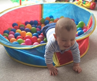 baby crawling out of indoor ball pool at home