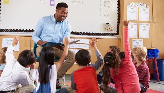 A black teacher in front of his class teaching