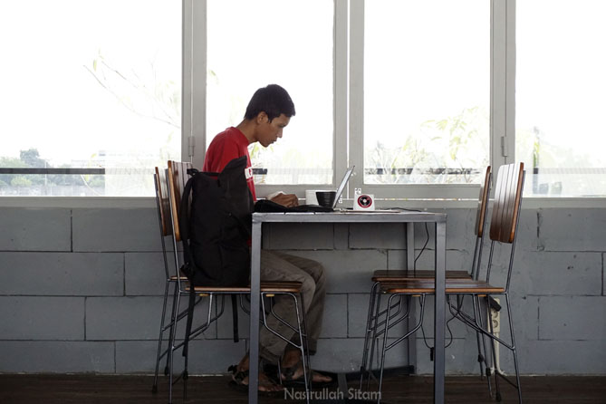 Menyelesaikan tulisan blog di kedai kopi