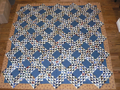 Scrap quilt of small blue and cream triangles form this traditional pattern