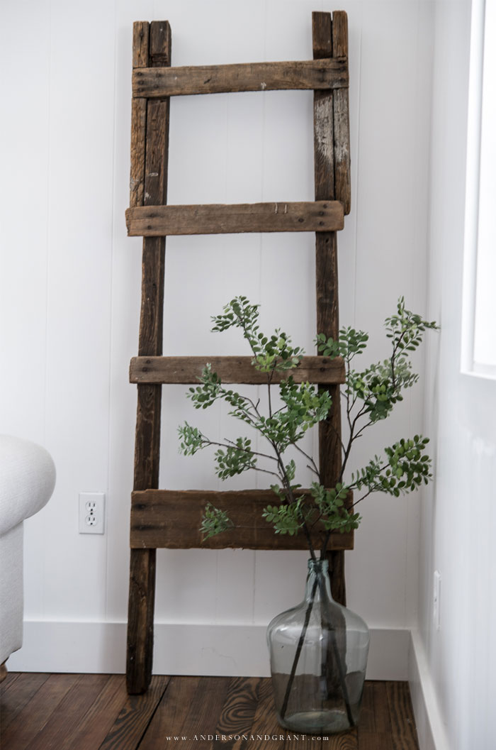 Antique wood ladder and greenery in demijohn