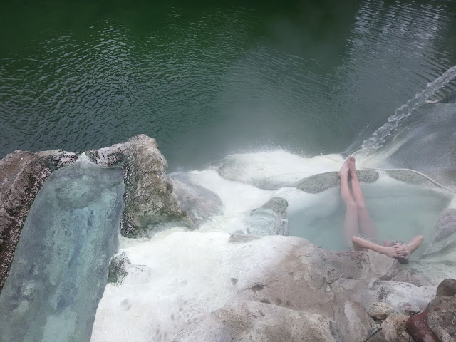 A woman in a natural hot tub on the Farma river in Petriolo
