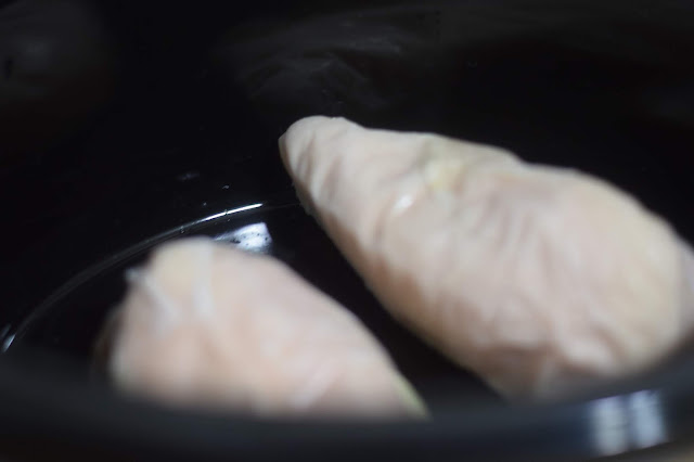 Frozen chicken breasts in the crockpot.