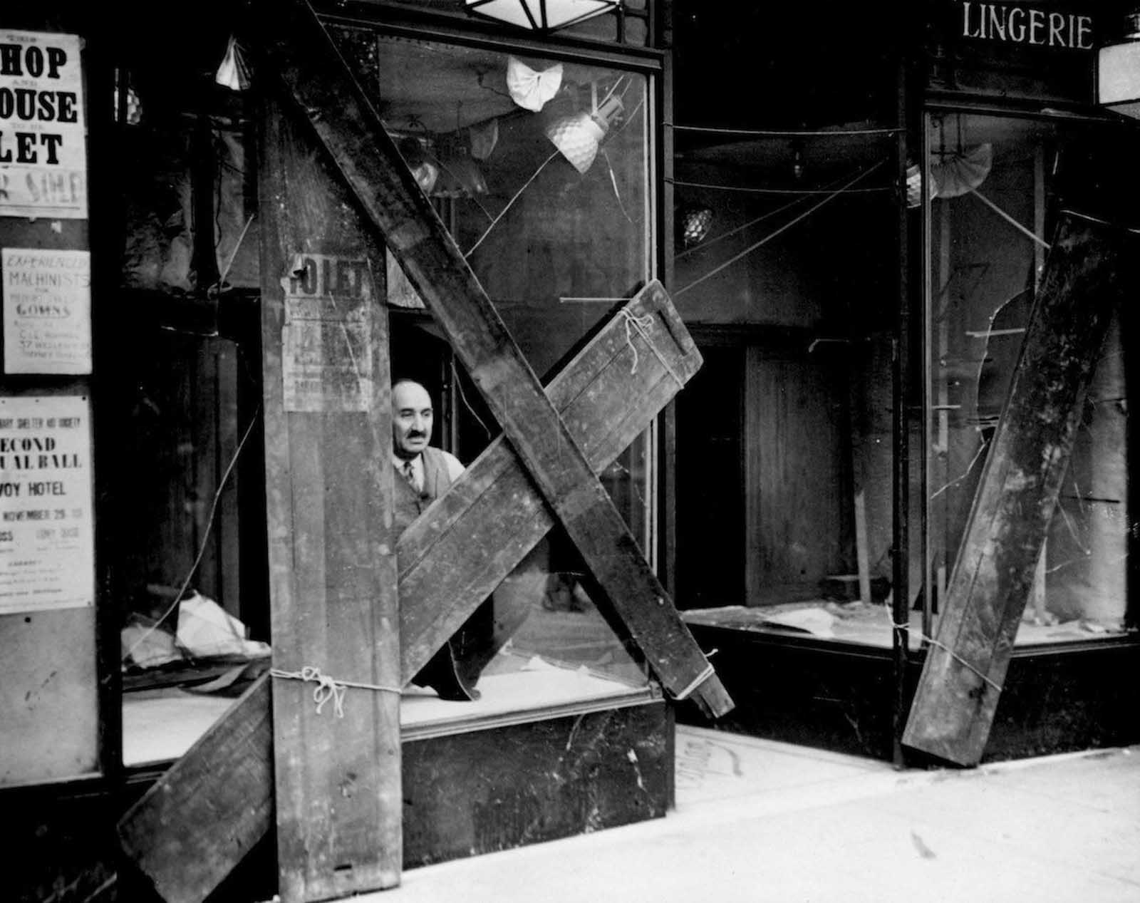 A Jewish shopkeeper peers out of his boarded up window in Mile End Road after a night of violence between Fascist and Communist factions in the East End. 1936.