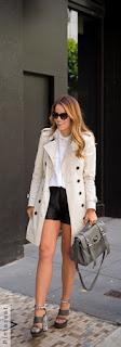 Mulher andando segurando uma bolsa cinza e usando uma sandália