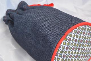 trousse baluchon, 26 cm de haut, 12 cm de diamètre, toile jean extérieur, tissu wax intérieur et fond, passepoil rouge, boutonnières et ruban rouge.