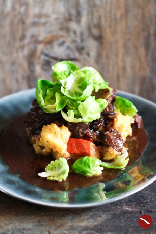 erfekt geschmorter Ochsenschwanz mit Cranberries, Kürbis-Kartoffelstampf, Rosenkohlblättchen und Maronen