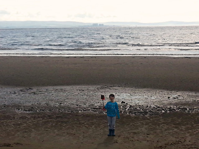 Boy standing on large beach, holding spade.