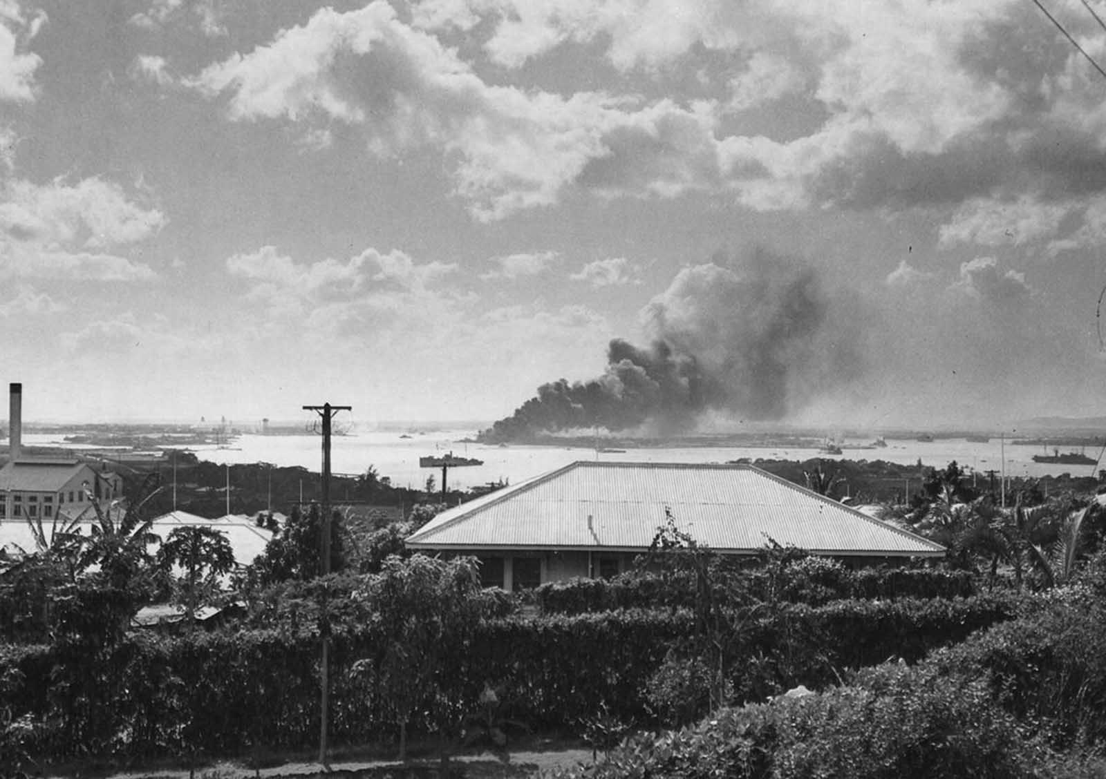 Seen from a distance, the Battleship Arizona burns as it sinks in Pearl Harbor after the December 7, 1941 raid by Japanese bombers.