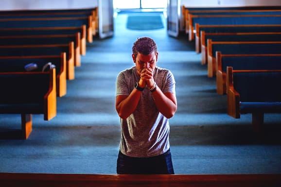 A imagem mostra um homem ajoelhado de mãos cruzadas em uma igreja em frente ao púlpito orando por seu pastor.