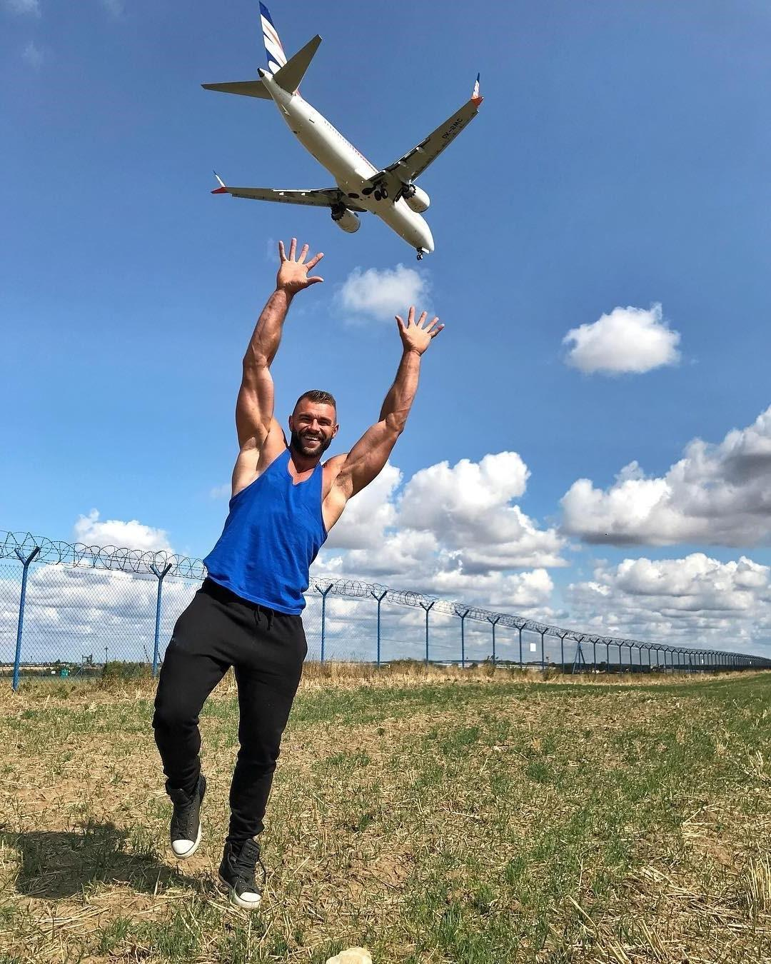 beefy-attractive-muscle-daddy-holding-huge-arms-up-smiling-airplane-flying-over
