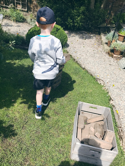 Little boy playing with large jenga blocks in the garden