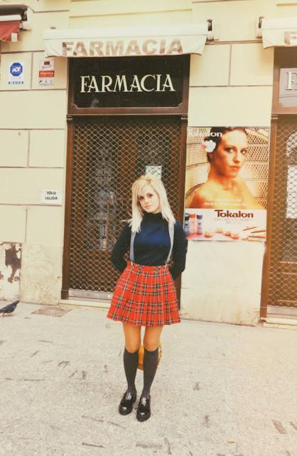 Alejandra Colomera vestida con jersey azul, falda roja cuadros escoceses, tirantes en color gris, calcetas gris y zapatos estilo colegial negro frente a farmacia antigua