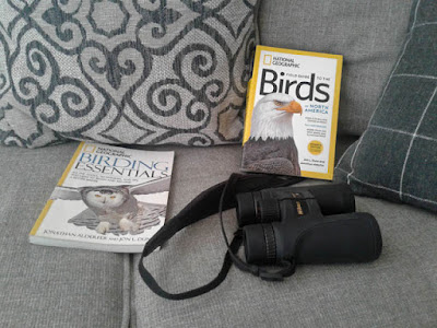 Photo of binoculars and bird books at home