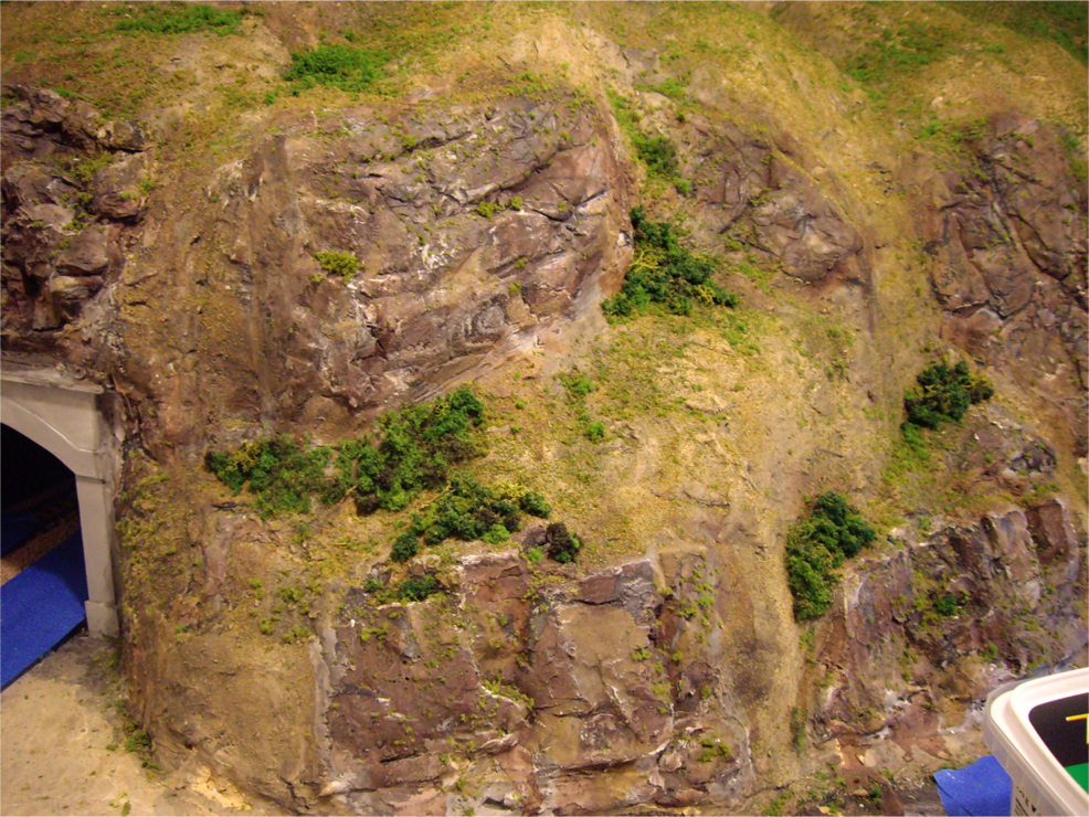 Painted plaster rock outcroppings and terrain with green ground foam being applied