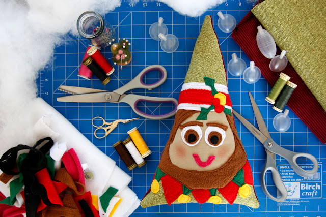 Homemade Christmas elf dog toy on a craft mat with sewing supplies