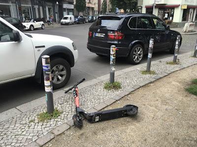 Liegender E-Scooter (an einer Kreuzung, zwischen zwei Autos)