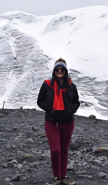 mulher jovem na neve vestida de calça da cor vinho e jaqueta preta