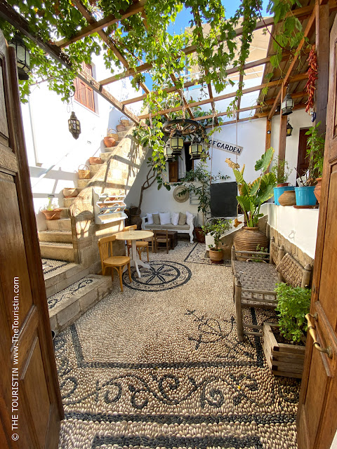 A courtyard, tiled with pebbles decorated with wooden furniture, colourful vases, overgrown by wine, with a stone staircase that leads to a rooftop terrace.