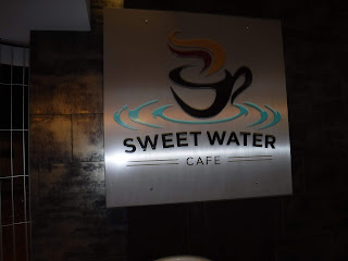 A silver metal sign with the SweetWater Cafe logo, a black coffee mug stting in blue ripples