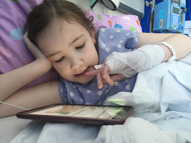 girl in hospital bed with cannula in