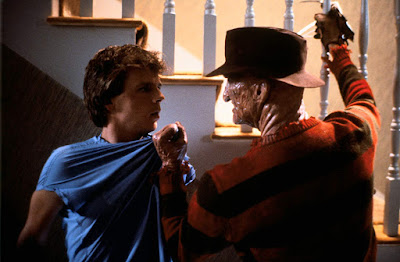 "Freddy Kruger (Robert Englund) grabs Jesse Walsh (Mark Patton) by the shirt and tries to kill him in the 1985 horror film ""Freddy's Revenge"""