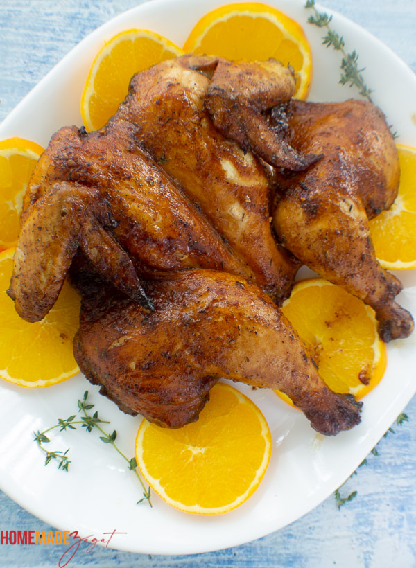 Finished roasted spatchcocked chicken on a white plate with orange slices.