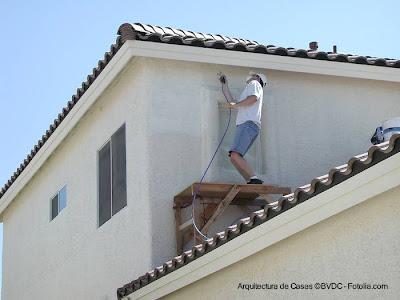 Pintor trabajando en las fachadas de una residencia