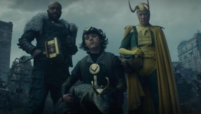 Imagem: três personagens em pé nos destroços de um mundo com prédios enormes e destruídos, um é um homem negro em uma armadura preta com um manto de pele branca, segurando um martelo de bronze como arma, um é o Kid-Loki, um garoto de cabelos pretos com um elmo de chifres dourados, roupas verdes e pretas segurando um crocodilo com um elmo de Loki, e ao lado, um outro Loki, com roupas verdes e amarelas berrantes, um elmo de chifres longos e velho.