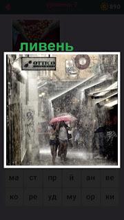 по улице в сильный ливень под зонтиком идут люди