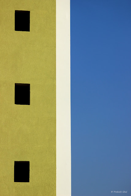 A Colorful look up Minimalist Photograph of Three Windows of a residential apartment in Jaipur City, against clear blue skies.