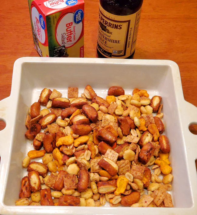 this is a casserole dish of nuts, pretzels and crackers in a butter sauce for snacking
